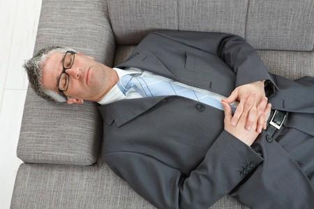 Müder Business-Mann liegt entspannt auf der Coach mit verschränkten Händen und meditiert. Meditation hilft ihm Ruhe zu finden.