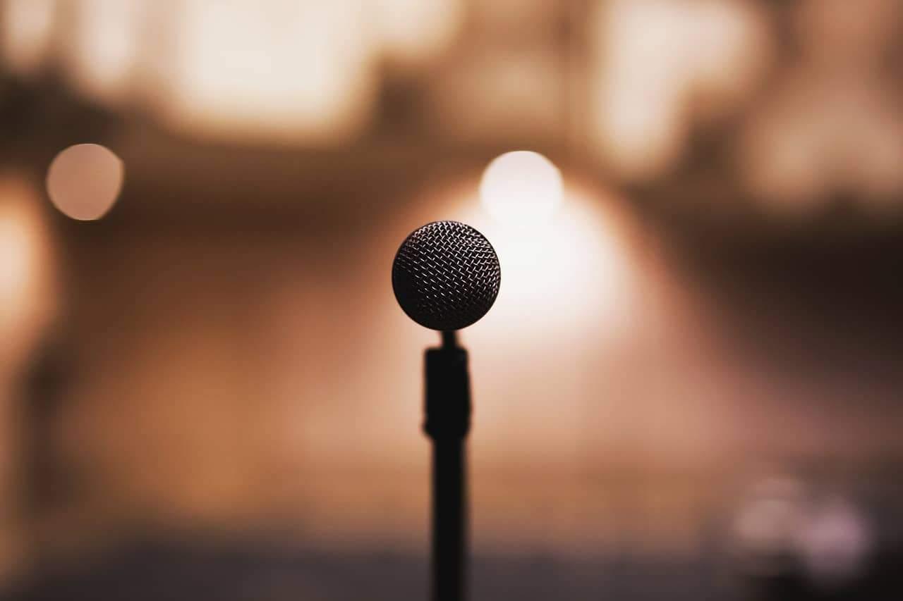 Ein Mikrofon, wie man es sieht, wenn man Keynote Speaker ist und vor vielen Leuten ein Referat hält. Im Hintergrund ist das Rampenlicht zu sehen.