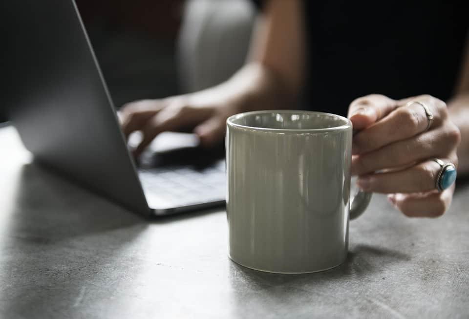 Eine graue Tasse mit Bulletproof Coffee und ein Notebook im Hintergrund. Eine Frau hat den Kaffee nach dem Rezept aus dem Internet hergestellt.