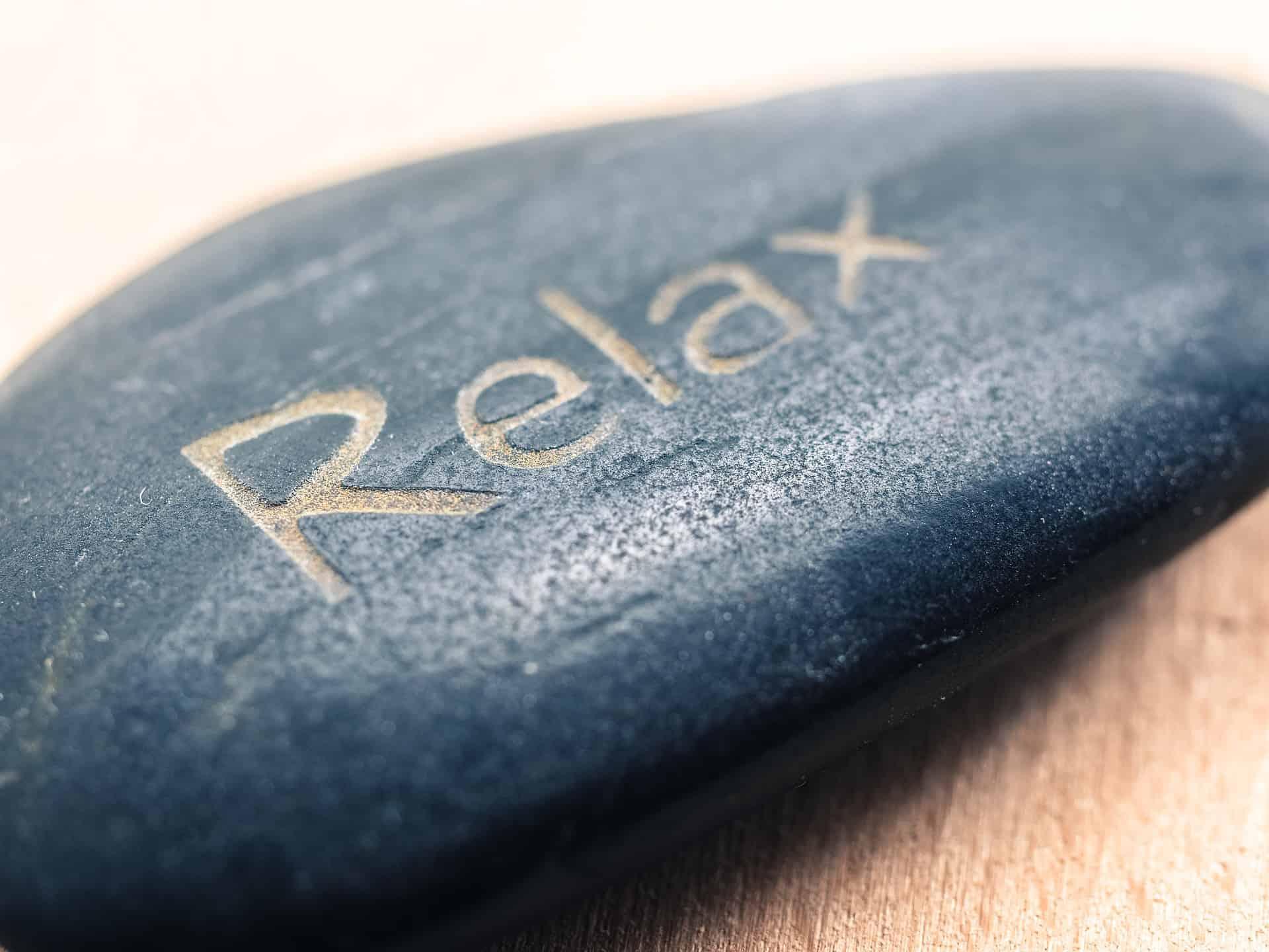 Entspannung geschrieben auf einen Stein. Diese Symbolik wird oft im Zen verwendet. Die Zenmönche sind Meister der Entspannung. Ihre Übung besteht aus einfacher Meditation und Gehen.