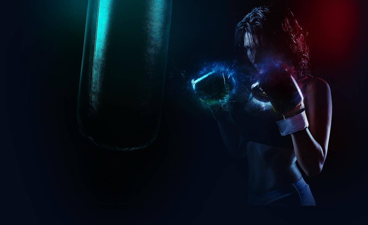 Frau beim Boxing-Workout. Die Farben zeigen die Anspannung, die Fäuste sind von einer Art blauer Aura umgeben. Wenn Du alles aus deinem Workout rausholen willst, dann brauchst Du Durchhaltevermögen, was man bei der Frau am Gesichtsausdruck erkennen kann.