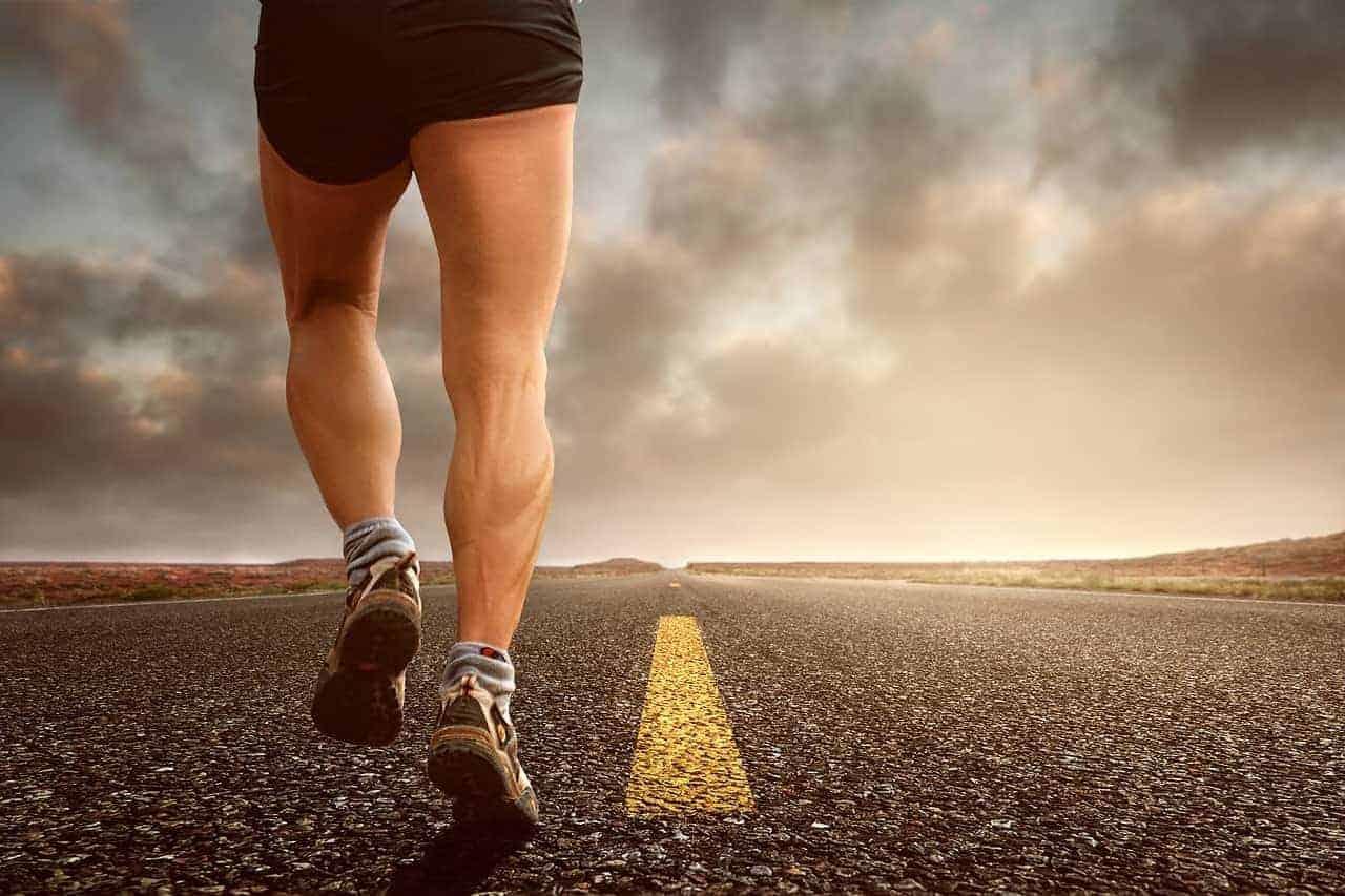 Ein Mann der beim Sonnenuntergang am Joggen ist. Für viele ist es nicht einfach nach einem harten Arbeitstag Motivation für das Training zu finden, daher läuft er ganz alleine dem Sonnenuntergang entgegen,