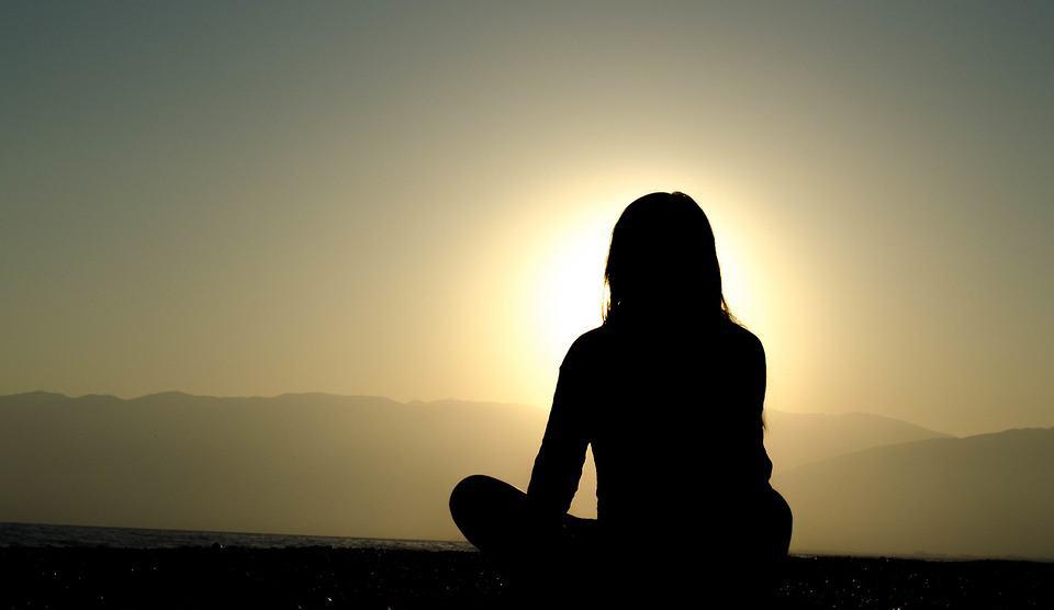 Meditation im Sonnenuntergang. Anfänger können oft nicht im ganzen Lotos sitzen und finden keine bequeme Position. Bei der Frau auf dem Bild ist zu erkennen, dass die Knie nicht am Boden sind, was eine entspannte Meditation erschwert. Daher sind für Anfänger meist kürzere Meditation-Sessions geeignet.