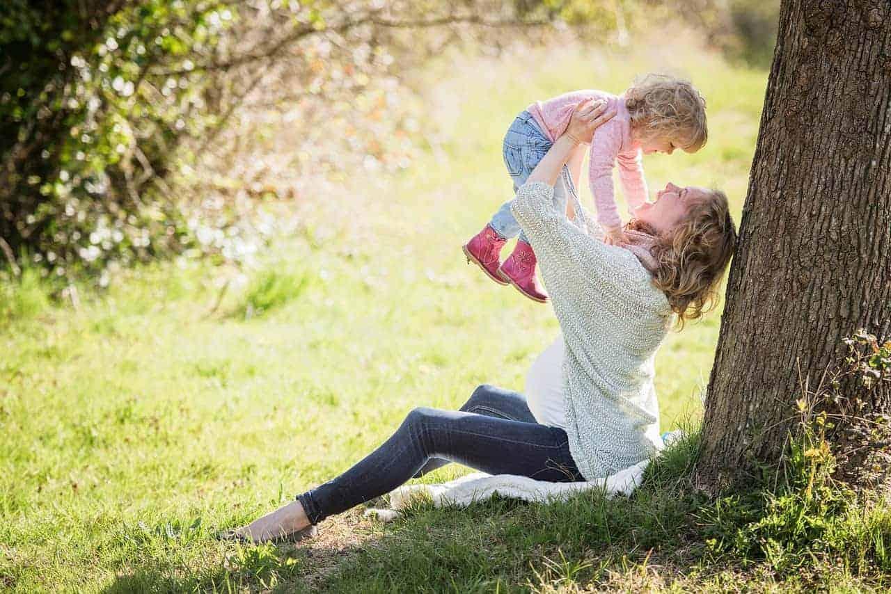 Eine Frau im Park, welche eine kleine süsse Tochter in die Luft hält und lacht. Klar ersichtlich ist, dass sie schwanger ist!
