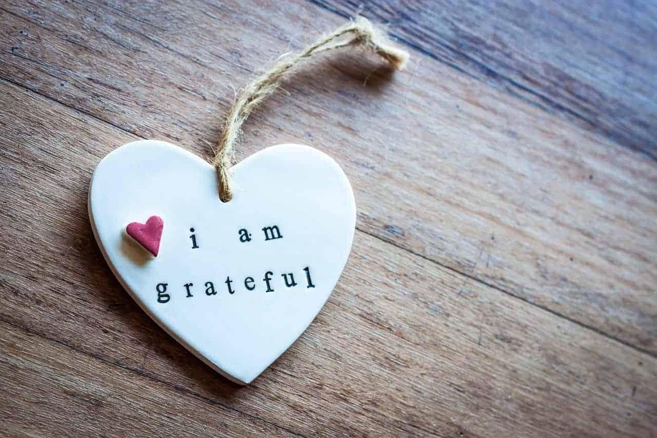 """Auf dem Bild ist ein hölzernes Herz mit der Aufschrift: """"Ich bin dankbar"""" in Englisch zu sehen. (i am grateful). Wertschätzung und Dankbarkeit sind in unserer westlichen """"konsumgesteuerten"""" Gesellschaft leider selten anzutreffen."""