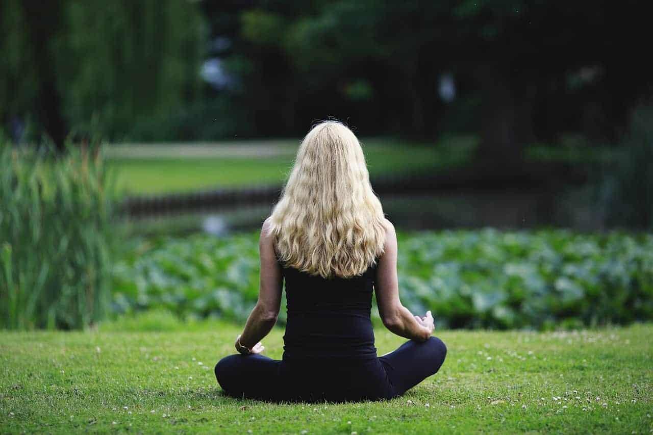 Eine blonde Frau sitzt in der Natur und meditiert. In der Meditation ist Achtsamkeit möglich - unabhängig von der Technik verändert sie die Wahrnehmung und hilft bei Mindfulness.