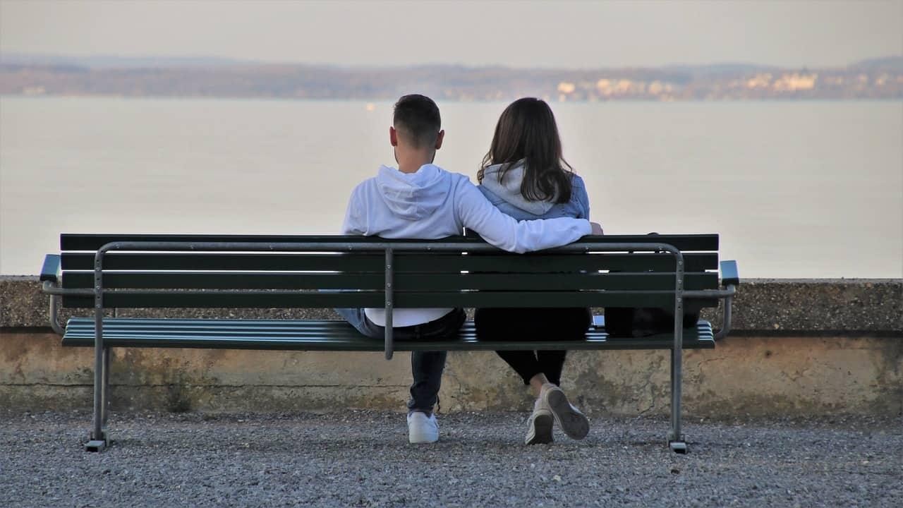 Ein Junge und ein Mädchen sitzen nebeneinander auf einer Bank und schauen entspannt dem Sonnenuntergang entgegen, da sie sich vertrauen.