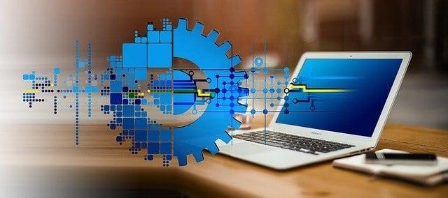 Die Digitale Transformation schematisch in Form von Zahlrädern und Schaltkreisen und einem Notebook dargestellt.