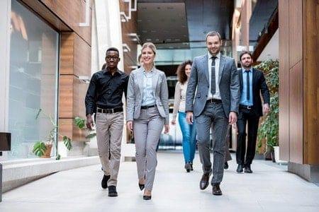 5 Personen in Business-Anzügen während der gehenden Meditation.