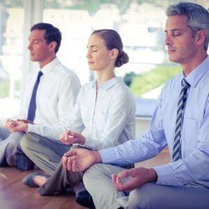 Drei Personen in tiefer Meditation am Boden sitzend.