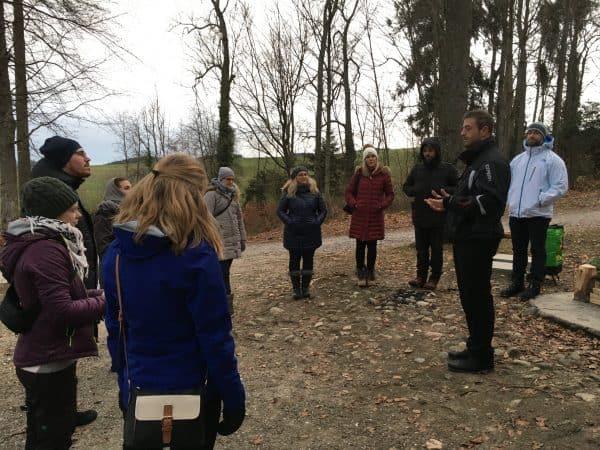 Marc Dietschi unterrichtet Meditation im Wald. Eine Gruppe von rund 10 erwachsenen Frauen und Männern hört ihm aufmerksam zu.