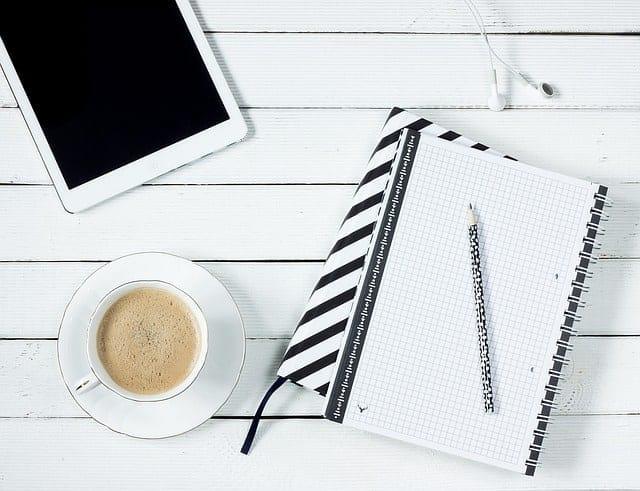 Mit Tablet, Kaffe und Notizblock auf eine Rede vorbereiten.