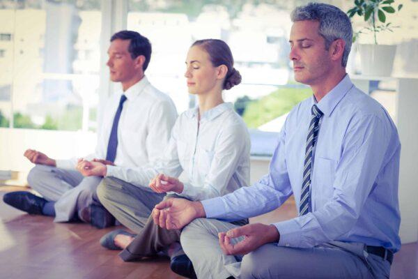 Drei im Business-Style gekleidete Personen in tiefer Meditation am Boden sitzend.