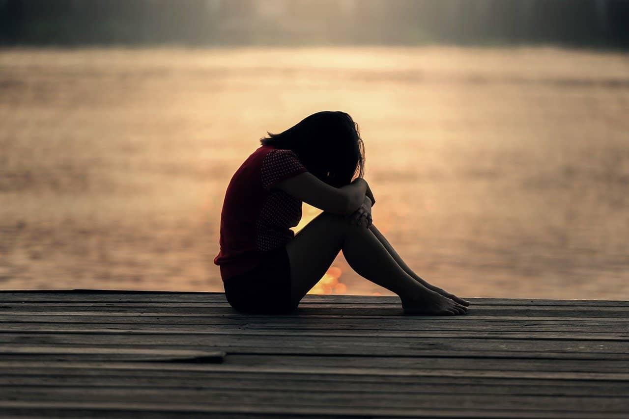 Junge Frau sitzt auf einem Steg an einem See im Sonnenuntergang. Eine von Natur aus entspannende Umgebung ermöglicht es ihr, komplett relaxed da zu sitzen.