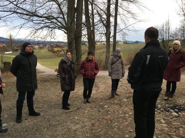 Marc Dietschi steht im Wald und unterrichtet eine Gruppe von Erwachsenen neue Meditationstechniken.
