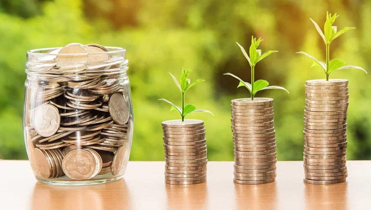 Türme aus Geldstücken, aus welchen kleine Pflänzchen wachsen und ein Krug voller Geld, welcher symbolisch für Reichtum steht.