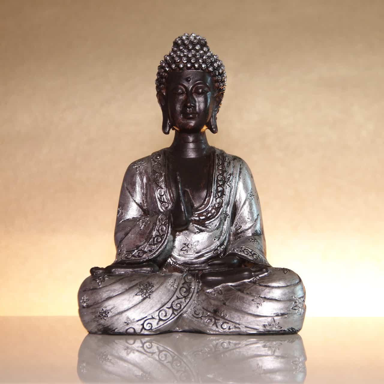 Silberne Buddha-Statue im Lotossitz sitzt auf einer spiegelten Oberfläche und goldener Rückwand.
