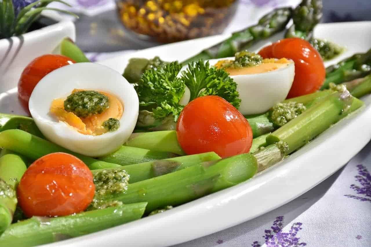 Ein weisser Teller mit Spargeln, Tomaten, Petersilie, Eiern und Pesto: Dies stellt aus Sicht der Ernährungspyramide der Schweiz, ein gesundes Menu dar.