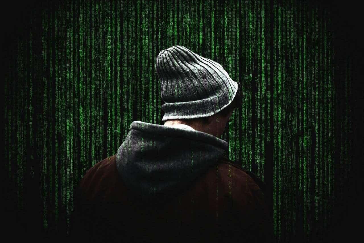 Person mit einer Mütze von Rücken her fotografiert. Sie steht im Matrix-Code, diesen grünen Zeichen auf schwarten Hintergrund. Das Bild soll zeigen, dass unser Universum ein System hat, und wenn man dieses durch die Meditation anfängt zu erkennen, Einfluss darauf nehmen kann.