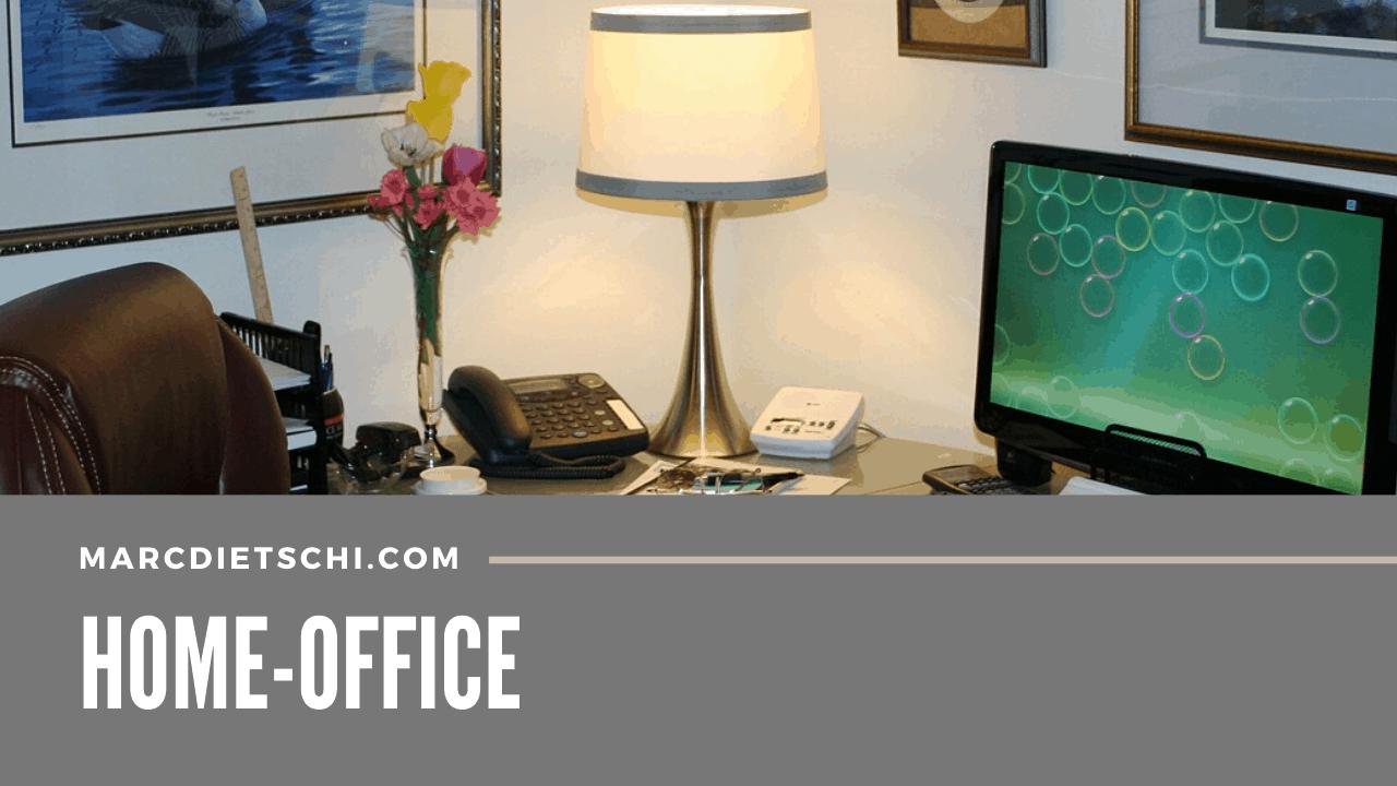 Pult, Computer, Telefon und Kampe im Home-Office. Es sind auch noch Blumen, Taschenrechner und Anrufbeantworter zu sehen.
